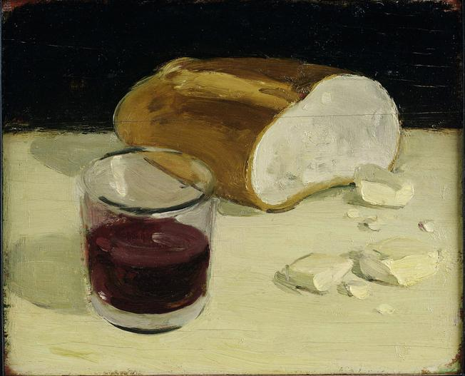 Cut loaf of bread, pieces of butter, and half filled cup of red wine on yellow table in front of black wall